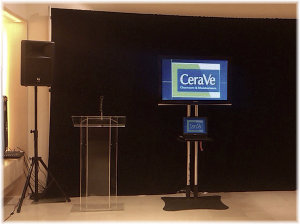Clear podium with microphone 52'' LED monitor on floor stand with connected laptop on the shelf and PA system setup.